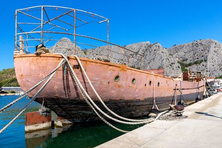 Old rusty barge ship near the city promenade. Omis. Croatia.