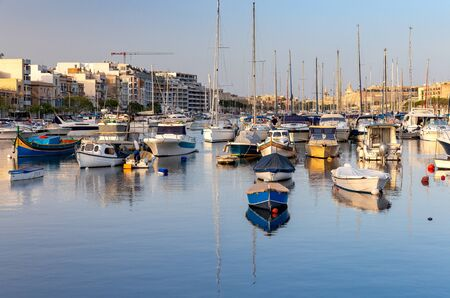Traditional multicolor Luzzu fishing boat and yachts in Valletta harbor. Malta.