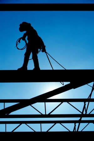 Silhouetted welder walks the high steel at a construction site