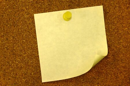Yellow curled blank memo on bulletin board with copy space