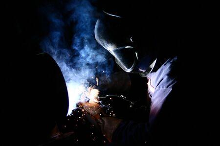 A welder arc-welds steel piping in a factory.