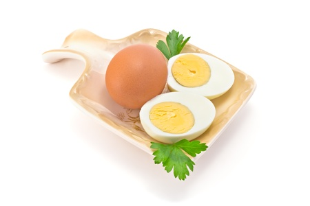 one egg, two halves of boiled eggs and parsley on the plate