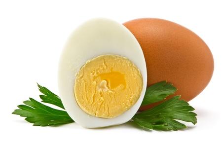 白い背景の上 1 つの卵と半分ゆで卵とパセリの葉します。