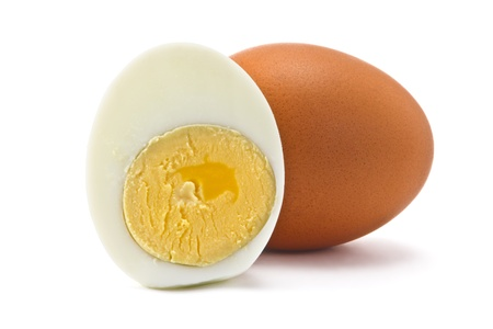 one egg and half a boiled egg on a white background