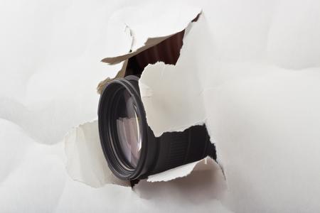 photo lens protruding through a hole paper