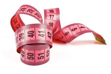pink tape measure twisted spiral on white background photo