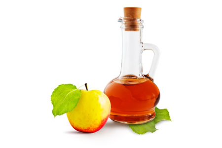 Apple cider vinegar cruet and ripe apples with green leaves on a white background