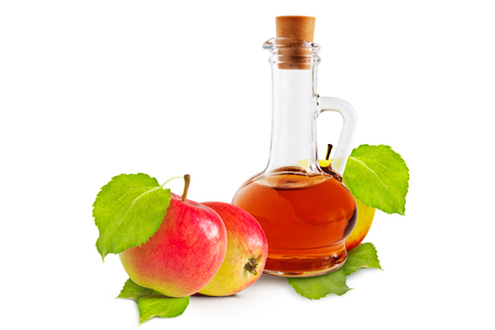 cruet: Apple cider vinegar cruet and ripe apples with green leaves on a white background