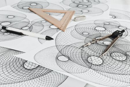 paper art projects: Circinus, ruler, pencil and eraser on a background sheet of paper with abstract geometric shapes Stock Photo