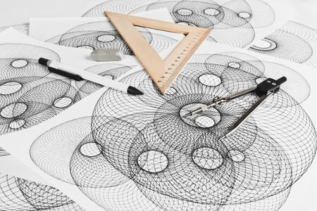 interweaving: Circinus, ruler, pencil and eraser on a background sheet of paper with abstract geometric shapes Stock Photo