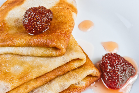 Pancakes with strawberry jam on a white plate