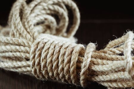 bonding rope: Twisted braided hemp rope close-up on a dark background Stock Photo