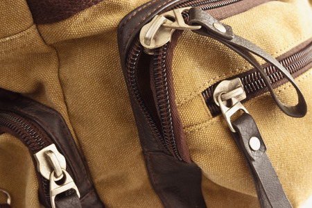 unzipped: Zip closure on the brown bag on her pockets
