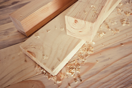 Planed board, a block and a little sawdust on a wooden surface in the carpentry workshop