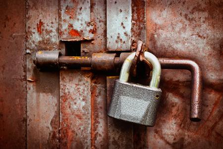 Lock and hasp on an old rusty iron gate closeup Фото со стока