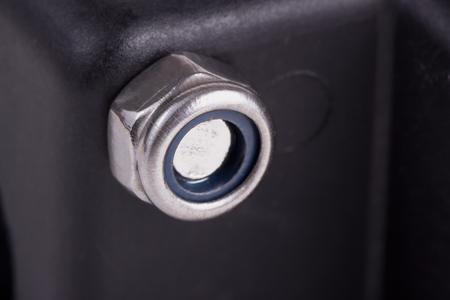 undulatory: Single metal self-locking nut on the black plastic surface