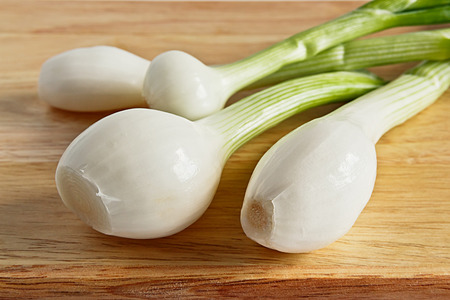 bulb and stem vegetables: Several young onions with green stems on a wooden surface