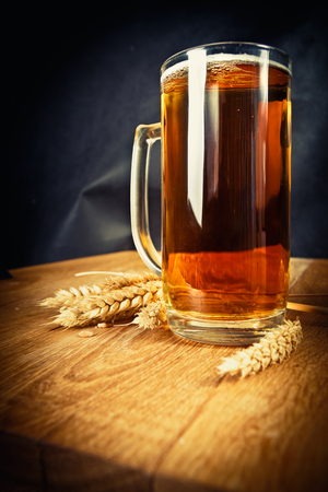 Mug of fresh beer and spikelet on the wooden table
