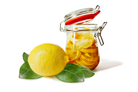pickling: Marinated slices of lemon in a glass jar, next to a lemon or half a lemon and green leaves on a white background