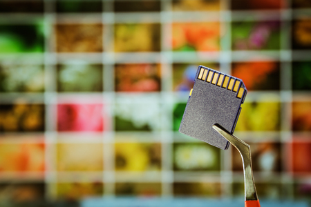 Digital memory card for photography and video. A storage medium on the background of a monitor with many photographs Stock Photo