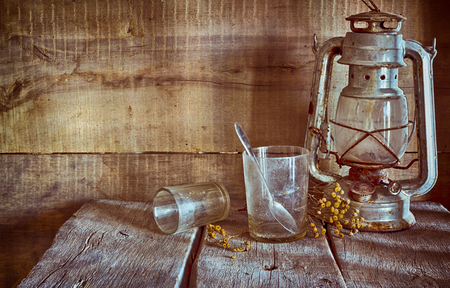 An old, dusty kerosene lamp called a bat in the corner of an old table on the background of a wooden wall