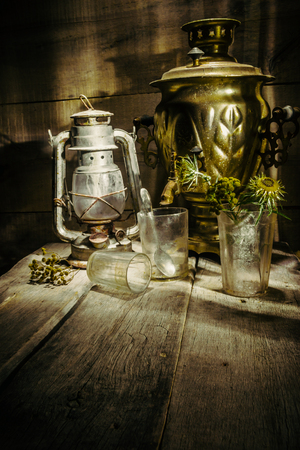 An old, dusty samovar, a glass with a spoon and a kerosene lamp in the corner of the old table on the background of a wooden wall
