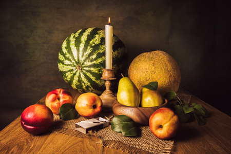 Fruit still life with pears, nectarines, melon, watermelon and candle in a carved candle holder Stock Photo
