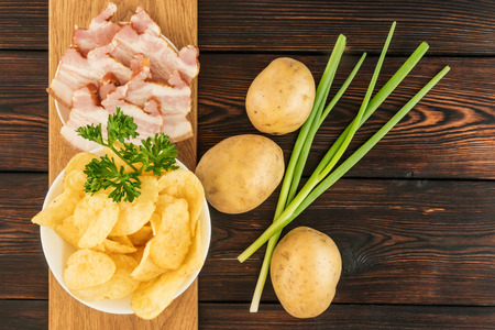 Still life with chips and raw potatoes, bacon and green onions on a dark wooden background Stock Photo