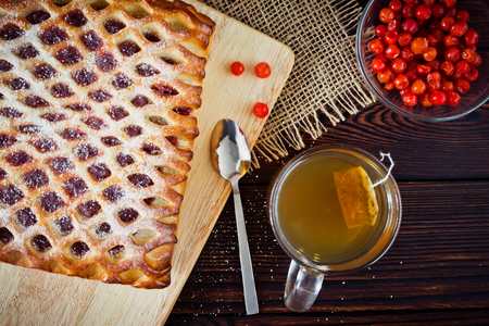 Berry pie, slices, mug green tea and red berry on a cutting board on a dark wooden background, top view