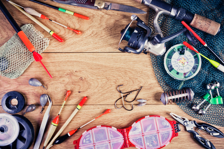 Fishing tackle - fishing, hooks, fishing line and floats, fishing rod with a reel, net, knife and other tools on a wooden background. Still life. View from above. Stock Photo