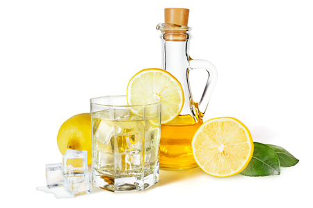 Lemon syrup in a decanter, a glass of lemonade with ice, lemons, ice cubes and green citrus leaves, isolated on a white background