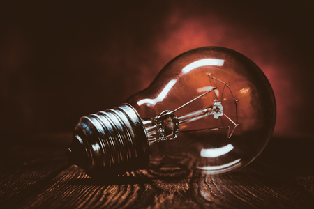 Incandescent lamp on a wooden surface on a dark red background