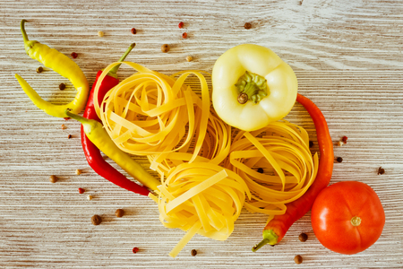 Flat noodles as well as chili pepper, sweet pepper and tomato on a wooden background Stock Photo