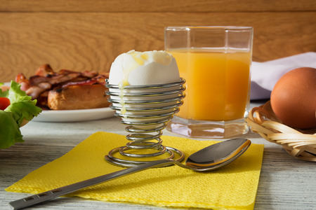 Light breakfast with a soft-boiled egg, bread and bacon, vegetables and fresh fruit juice