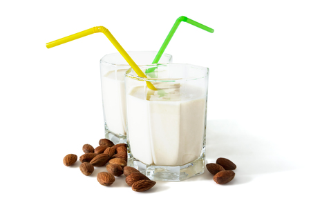 Almond milk in spectacular glasses with cocktail tubes and almonds isolated on white background Фото со стока