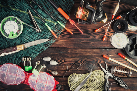 Fishing tackle - fishing, hooks, fishing line and floats, fishing rod with a reel, net, knife and other tools on a wooden background. Still life. View from above. Фото со стока