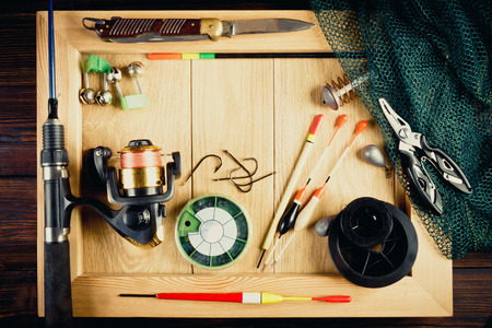 Fishing tackle - fishing, hooks, fishing line and floats, fishing rod with a reel, net, knife and other tools on a wooden background, in a frame. Still life. View from above. Фото со стока