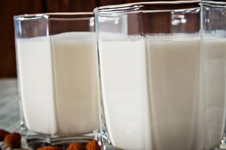 Almond milk in transparent glasses with cocktail tubes and almonds on a wooden background