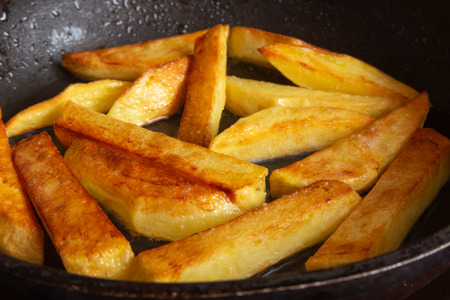 Fried potatoes in a skillet in hot oil with crispy crusts Фото со стока - 120886964