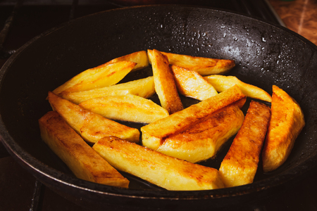 Fried potatoes in a skillet in hot oil with crispy crusts
