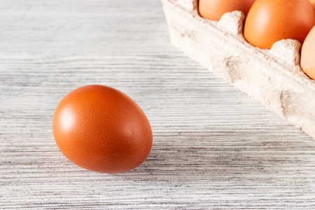 Eggs in a tray and a lonely brown egg on a wooden gray background Фото со стока - 120886969