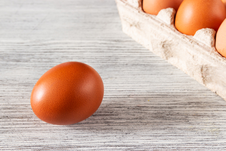 Eggs in a tray and a lonely brown egg on a wooden gray background Фото со стока - 120886973