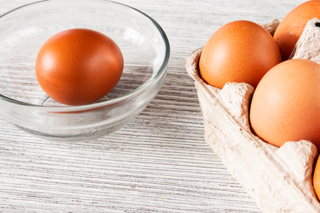 Eggs in a tray and a lonely brown egg on a wooden gray background