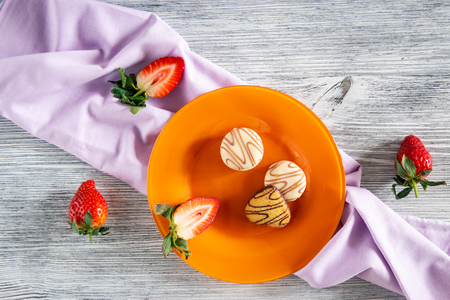 Cookies and strawberries in a plate on a napkin on a wooden background with a yellow tulip, still life Фото со стока - 120886979