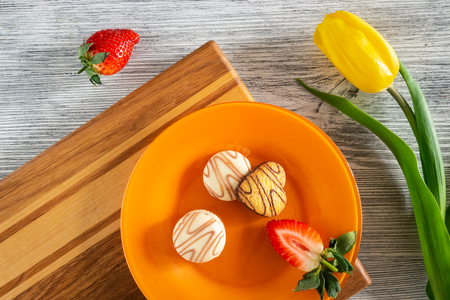 Cookies and strawberries in a plate on a cutting board on a wooden background with yellow tulip, still life Фото со стока
