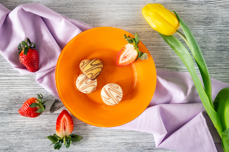 Cookies and strawberries in a plate on a napkin on a wooden background with a yellow tulip, still life Фото со стока
