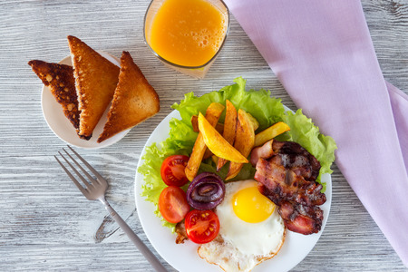 Hearty breakfast fried eggs with bacon fried potatoes with slices of tomatoes on lettuce leaves