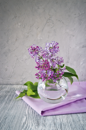 Sprig of lilac in a glass round vase on a wooden table still life