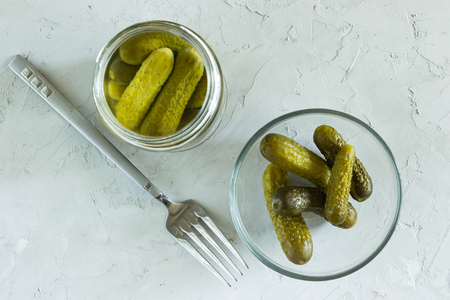 Gherkins marinated in a glass jar and in a bowl on a gray concrete background Imagens