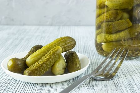 Pickled gherkins in a glass jar and in a bowl on a gray wooden background